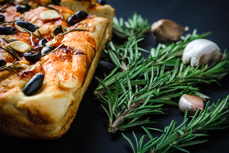 Traditional Italian vegetarian focaccia of homemade bread with olives and rosemary on black background.