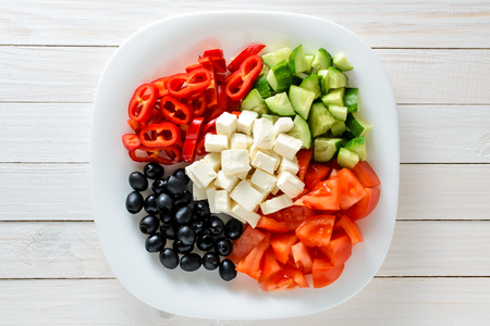 Fresh vegetables and cheese in a plate on a wooden table. Healthy food, ingredients for Greek salad, top view