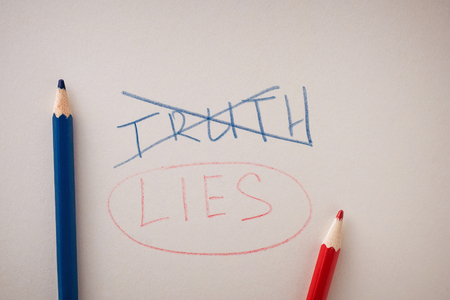 The crossed out word truth and the underlined word lies on paper. The concept of replacing true with lie