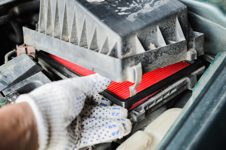 Car service. The mechanic replaces air filter. Closeup photo Banco de Imagens