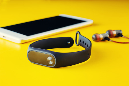 Fitness tracker, headphones and smartphone on yellow background close-up