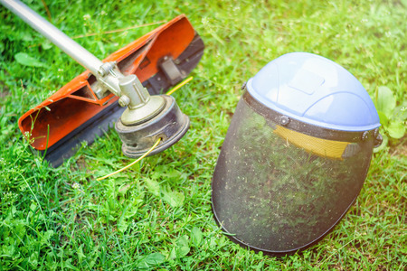 String trimmer and protective face mask on grass Archivio Fotografico