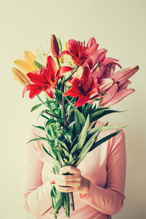 girl holds bouquet of lilies in her hands, hides face in flowers. Toned photo