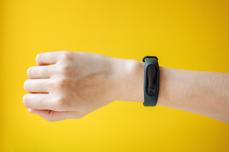 Woman's hand with fitness tracker on yellow background close up