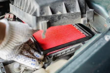 The mechanic replaces air filter in car. Installing new filter in engine