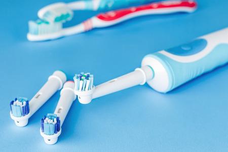 Elektrische und manuelle Zahnbürste auf blauem Hintergrund, Nahaufnahme