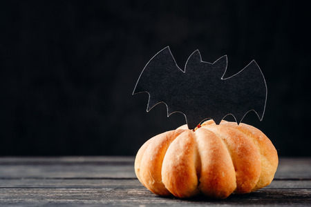 Homemade halloween cake in shape of  pumpkin on dark background with copy space. Hallooween sweets