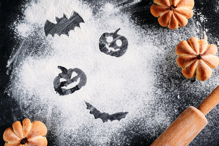 Drawing Halloween decorations on flour background, cakes in shape of pumpkin and rolling pin. Halloween cooking concept