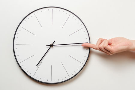 Woman hand stop time on round clock, female finger takes minute arrow of the clock back, time management and deadline concept Stock Photo