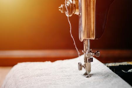 Teil einer Vintage-Handnähmaschine und eines Kleidungsstücks. Stahlnadel mit Greifer- und Nähfußnahaufnahme. Standard-Bild