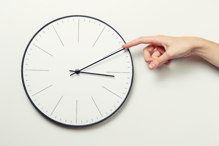 Woman hand stop time on round clock, time management and deadline concept Stock Photo