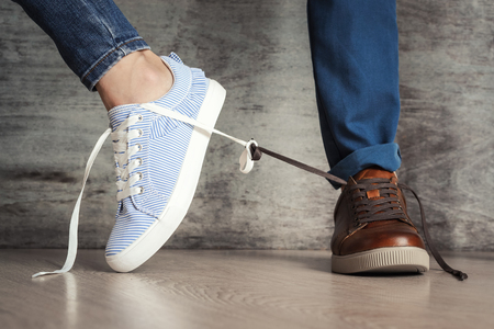 Women's shoe goes away from men's. Concept of breaking family relationships or quarrels Stockfoto