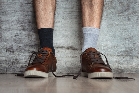 Man legs in brown leather shoes and different socks on dark background, close up. Concept of strange idiot man 版權商用圖片