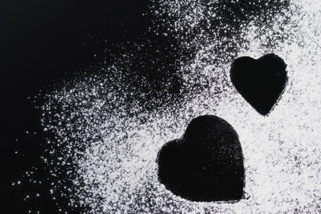 Baking background with heart shape and flour on dark table with copy space, top view