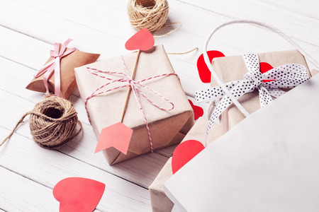 gift boxes, paper cut heart and shopping bag on white wooden background. Valentine's Day decorations