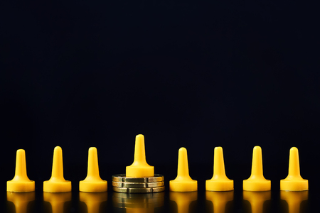 Income differences between rich and poor concept. Board game figure on pile of coins and   crowd from other figures Stock Photo