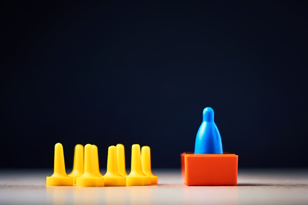 Leadership and success concept.  Board game figure towers above the crowd of other chips Stock Photo