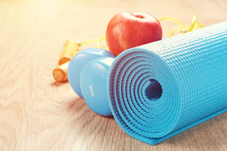Fitness concept with blue dumbbells and yoga mat