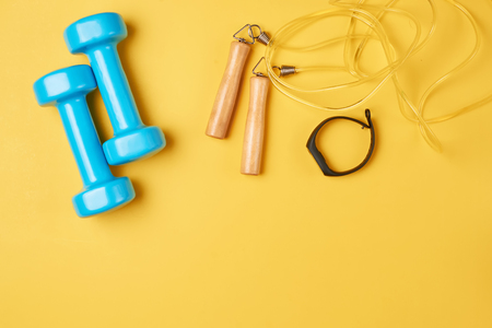 Flat lay composition of blue dumbbells, jump rope and fitness tracker on yellow background with copy space