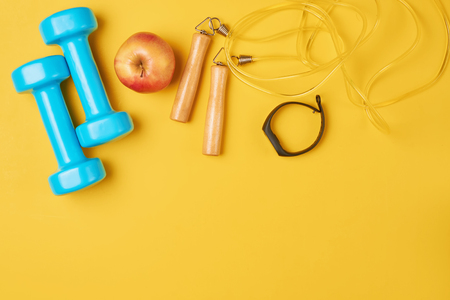 Fitness concept with blue dumbbells, skipping rope and fitness tracker on yellow background, top view flat lay