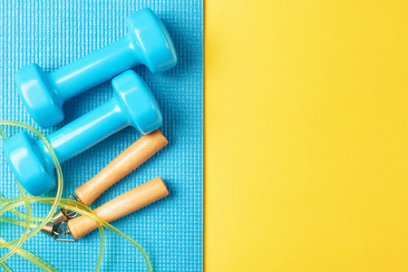 Flat lay, top view minimal background, fitness concept. Blue dumbbells and jump rope on blue and yellow background