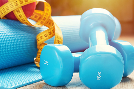 Fitness concept with blue dumbbells, fitness mat and measuring tape, close up