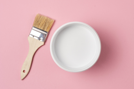 Brush and paint can with white color on yellow background, top view Standard-Bild - 116475121