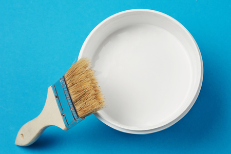 Brush and paint can with white color on blue background, closeup Standard-Bild - 116496120