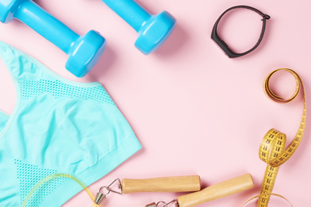 Sport bra, dumbbells, measuring tape, jump rope and fitness tracker on pink background, top view with copy space. Fitness and body care concept