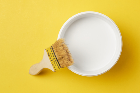 Brush and paint can with white color on yellow background, top view Standard-Bild - 116496127