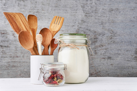 Kitchen utensils background with wooden cutlery in ceramic cup on white table