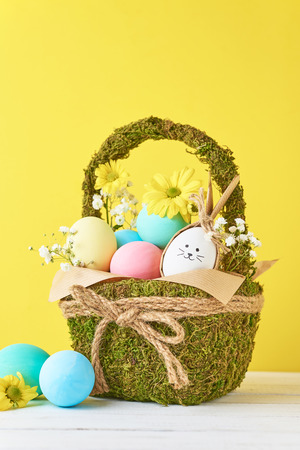 Colorful easter eggs in decorative basket on yellow background