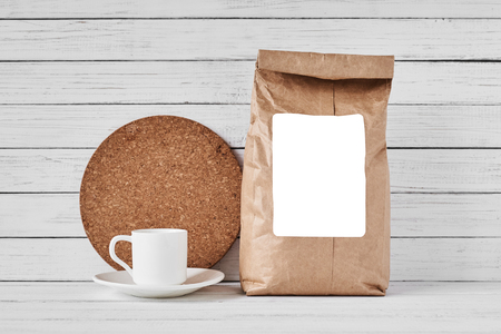 Craft paper bag with copy space and coffee cup on white background