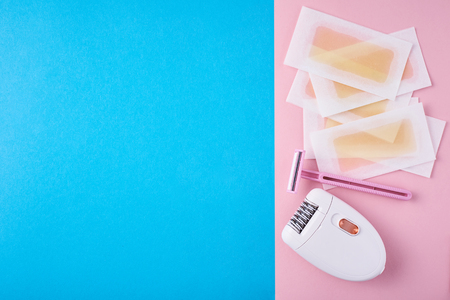 Epilator, razor for shaving and wax strips on blue and pink background with copy space. Set for depilation, bodycare concept Stockfoto