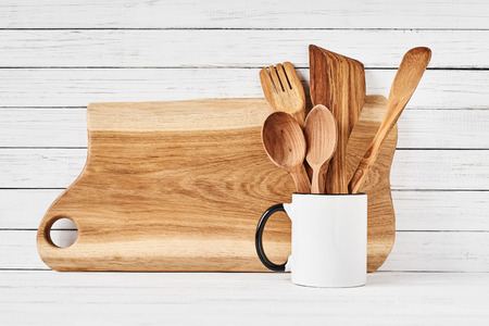Cooking utensils and cutting board on white table. front view. Kitchen utensils background Imagens