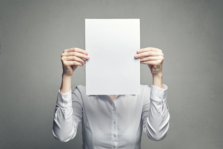 anonymous business woman in white blouse covering face with white paper sheet