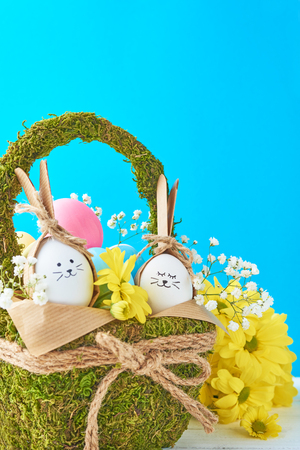 Easter concept. Eggs in basket decorated with flowers on blue background