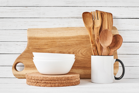 Cooking utensils and cutting board on white table. Kitchen utensils background