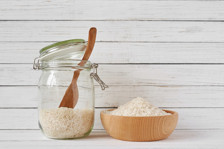 Rice grains in wooden bowl and glass jar on white background Reklamní fotografie