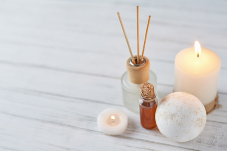 Spa treatment composition. Burning candle, massage oil and aromatherapy wooden sticks with copy space