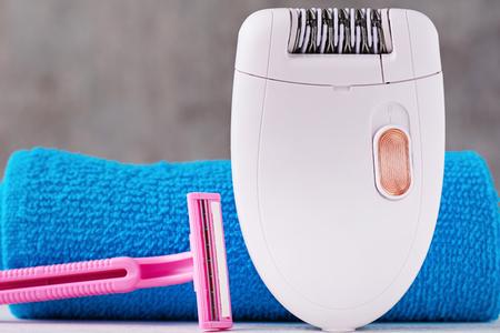 Epilierer und Rasiermesser im Hintergrund mit Shampoo und Handtuch, selektiver Fokus