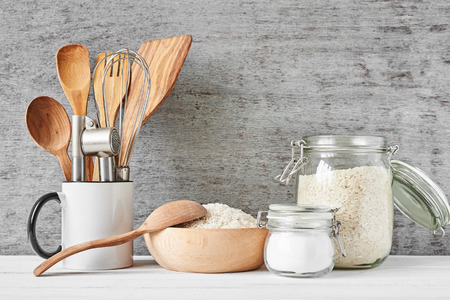 Kitchen utensils and glass jar with rice on gray wall background