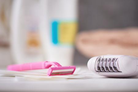 Epilierer, Rasiermesser und Wachsstreifen auf dem Hintergrund mit Shampoo und Handtuch, selektiver Fokus