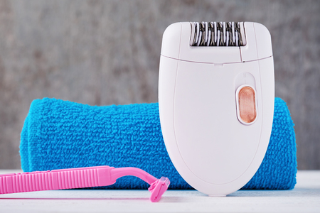 Epilator and shaving razor on background with shampoo and towel, selective focus