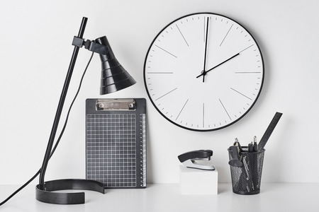 Office supplies, table lamp and wall clock on white background, front view. Home workplace