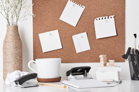 Korktafel mit Bürobedarf, Tasse und Pflanze in Flaschenvase auf weißem Hintergrund, Vorderansicht. Homeoffice-Arbeitsplatz