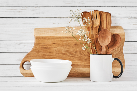 Kitchen tools and cutting board on white table. Kitchen utensils background Imagens