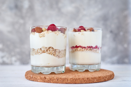Two glasses of greek yogurt granola with raspberries, oatmeal flakes and nuts on white background. Healthy nutrition