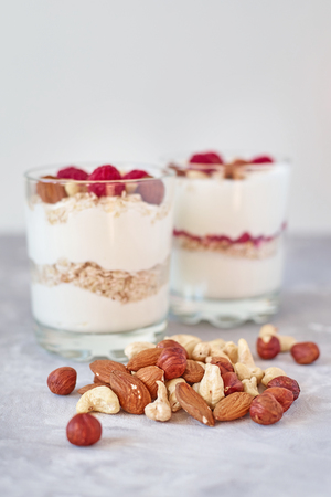 Two glasses of greek yogurt granola with raspberries, oatmeal flakes and nuts on white background. Healthy nutrition Imagens - 121717313