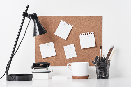 Cork board with office supplies, cup and lamp on white background, front view. Home office workplace